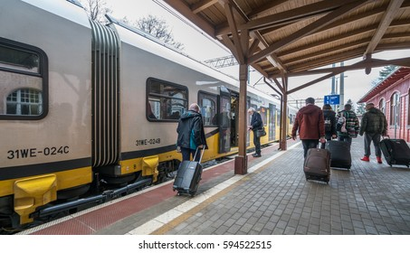 Szklarska Poreba, Poland -  February 2017 :  Tourists with wheeled luggage cases boarding ready to depart local train standing on a platform on the train station in Szklarska Poreba, Poland