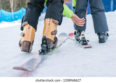 Szklarska Poreba, Poland - February 2019 : Ski instructor helping his adept young student to attach leg with ski boot into the lock on the ski