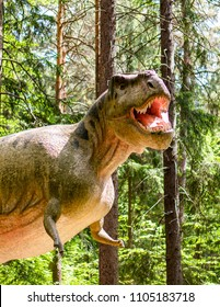 Szklarska Poreba, Poland - May 10, 2018: Tyrannosaurus Rex model with open mouth and sharp teeth with trees in the background at the Dino Park