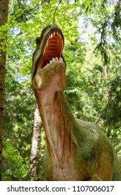Szklarska Poreba, Poland - May 10, 2018: Allosaurus model with open mouth and sharp teeth with trees in the background at the Dino Park