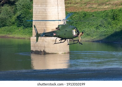 Szolnok, Hungary - August 20, 2019: Hungarian Air Force Airbus Helicopters Eurocopter AS350 H125M Ecureuil 102 military helicopter drops a military diver into tisza river