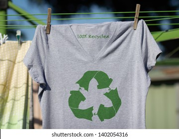 T shirt hanging on line with Recycled text, recycling clothes and textiles icon, ethical shopping sustainable fashion concept