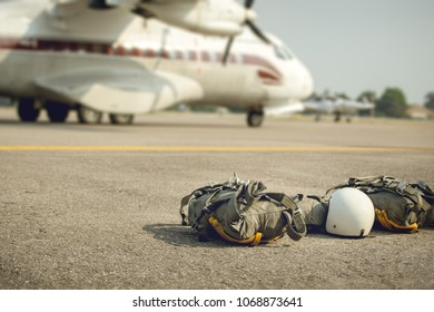 T-10 parachute with helmet and equipment for paratroop stanby on ground near military transport propeller aircraft for mission in cinematic tone with copy space