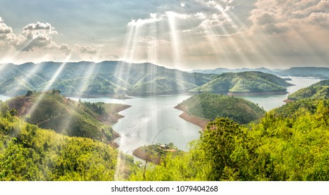 Ta Dung lake in the morning when sun rays at the top of the mountain shines fog into the lake full of mist and small islands paradise. This is the reservoir for hydropower in Dac Nong, Vietnam.