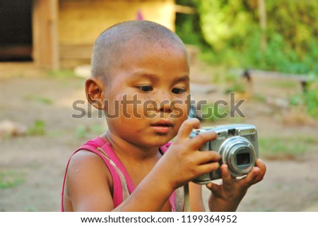 Ta Seng, Cambodia - April, 2010: Young small boy in the courtyard of a poor rural village holding and looking at a silver Canon digital camera trying to take pictures. He looks concentrated playing