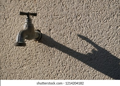 Tab water metal valve outside the concrete wall building created dark shadow