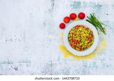 Tabbouleh - Levantine vegetarian salad made of chopped parsley, tomatoes, onion, bulgur or couscous and served with olive oil, lemon juice, salt and pepper. Space for text. Top above view