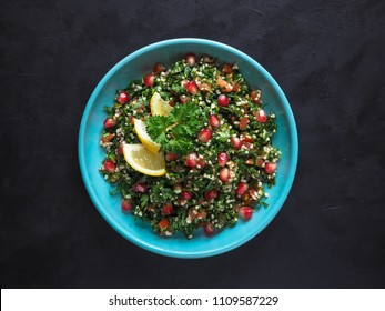 Tabbouleh salad with couscous in a bowl on the black table. Levantine vegetarian salad with parsley, mint, bulgur, tomato.