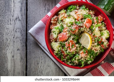 Tabbouleh salad with couscous in red bowl on rustic table. Top view