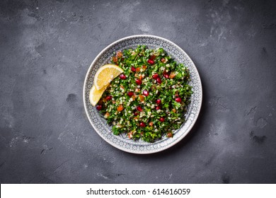Tabbouleh salad on plate, rustic concrete background. Traditional middle eastern or arab dish. Levantine vegetarian salad with parsley, mint, bulgur, tomatoes. Part of middle eastern meze. Top view