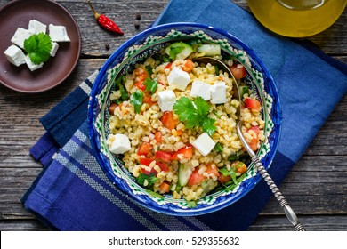 Tabbouleh salad with tomato, olive oil, parsley and pomegranate seeds served in ethnic middle eastern bowl on rustic table. Top view