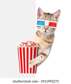 Tabby cat wearing 3d glasses holds popcorn anf looks dron behind empty white banner. isolated on white background