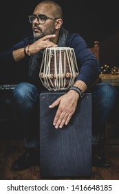 Tabla and Cajon - Indian and Peruvian drums used to make fusion percussion music. Man in background attempts to play the instruments.