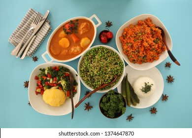 Table From Above With African Food. Chicken Stew, Jollof Rice, Pilau Rice, Spinach Rice, Plantains Chili, Coriander, Salad, Pepper. Blue background.