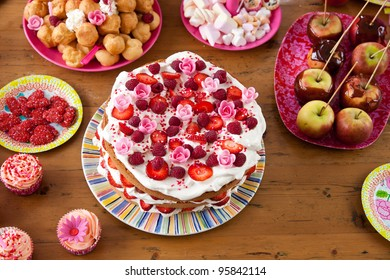 A table with all kinds of sweet treats like cakes and candy