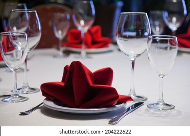 table appointments. Hotel service: table in a restaurant with a white tablecloth, red napkins, wine glasses and cutlery.