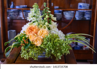 Table arrangement of cut flowers including roses, foxgloves, hydrangeas, costa, euphorbia and liriope leaves