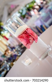 Table arrangement of flower petals in water with candles