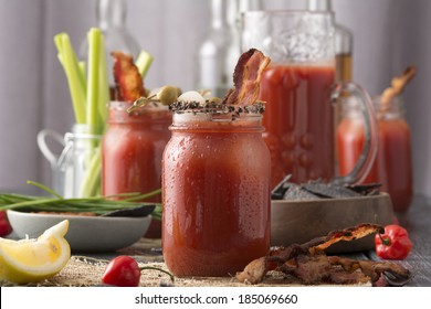 Table arrangement with pepper smoked bacon bloody mary or caesar in mason jars