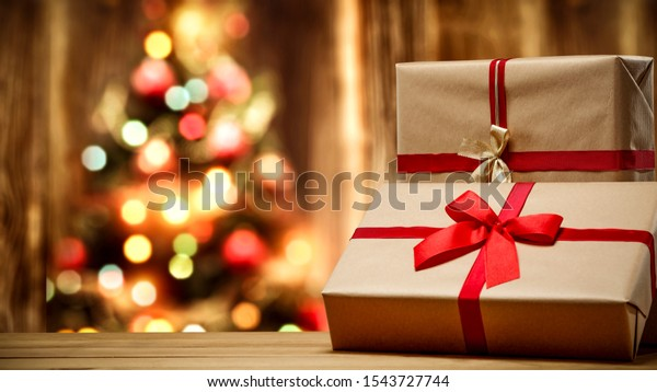 Table background of free space and christmas gifts. Xmas tree and wooden blurred wall.
