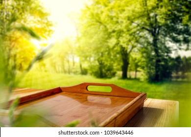 Table background of free space and kitchen board and landscape of spring garden with sun and leaves.