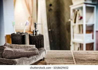 Table background of free space for your product and blurreed interior of bathroom. Towels decoration on top.