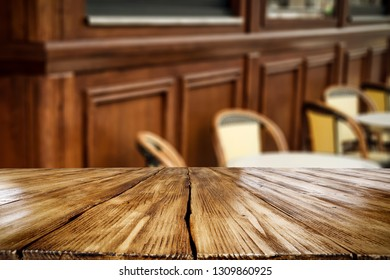 Table background of free space for your decoration and wooden blurred background of wall and chairs