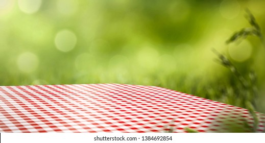 Table background of free space for your decoration. White and red tablecloth and green blurred background of grass and sun light. Summer time