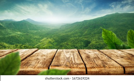 table background of free space for your decoration and blurred landscape of mountains.Blue sky with sun light and green small leaves.  - Shutterstock ID 1672619224