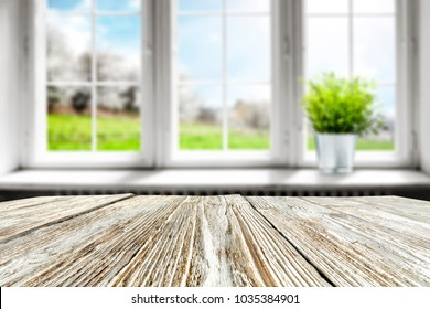 Table background in kitchen and blurred window space with small green plant on window sill.