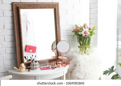 Table with beautiful mirror and cosmetics in modern makeup room