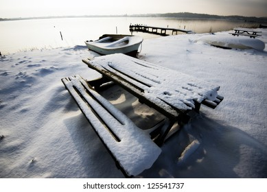 Table and bench covered in snow close to beach and small wooden bridge