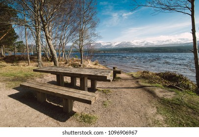 Table and bench on the shore of the lake, Aviemore, Scotland.