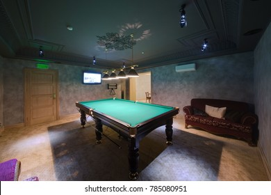 A table for billiards, a dark sofa and the TV in the restroom