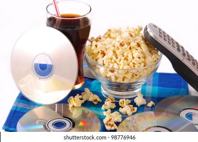 table with bowl of popcorn,cold drink,dvd discs and remote control