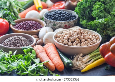 A table with bowls of beans and mixed vegetables