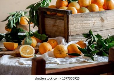 Table with box of fresh orange with orange tree branch and fresh orange juice