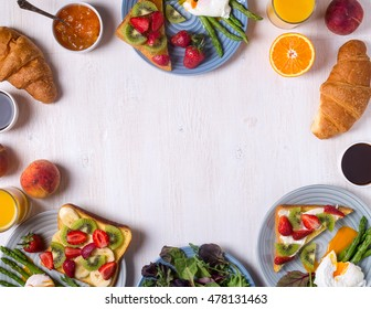 Table with breakfast - asparagus with poached eggs , toast with fruit, croissants, coffee, juice, top view.