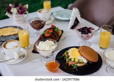 Table for breakfast, orange juce, omelette on a white table