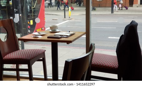 A table in a cafe with a coffee cup, diary and mobile phone on it. Two empty chairs, one with a suite jacket over the back. A view of the back of a red bus and people walking past out of the window.