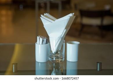 Ein Tisch in einem Café oder Restaurant. Weiße Servietten in einer Metallserviette, Gewürzsalz und Pfeffer auf einem Holztisch, Panoramablick. Zahnstocher