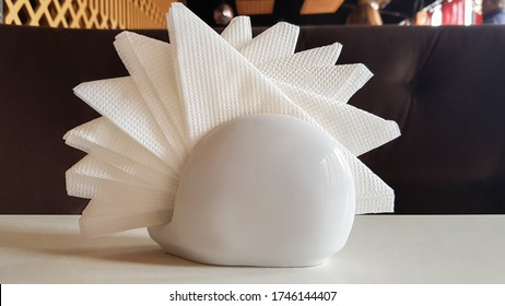 A table in a cafe and restaurant. White napkins in a ceramic napkin holder. Hotel dining table with napkins. A paper napkin is placed in a glass on a table in the banquet room.