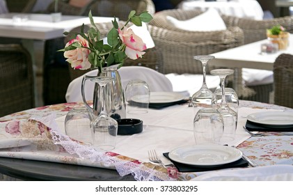 table in a cafe, serving table in a cafe, Empty outdoor restaurant table, Empty glasses in restaurant, dwarf tree on a table in a cafe, roses in the vase on table