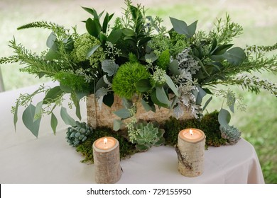 table centerpiece with dar green floral arrangement