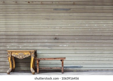 A table and chair against a beautiful wall in the streets of China.