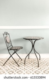 Table and chair with mosaic pattern in  the room , blue panel and tile floor.