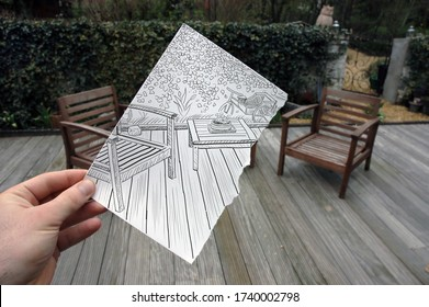 Table and chair sketched on a hand held piece of paper with wooden terrace and garden in the photo background. Mixed media image.