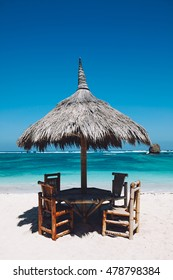 Table and chair with straw umbrella on the tropical white sand beach with turquoise water on island in Asia