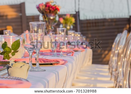 table and chairs baby or bridal shower event decor with glasses and pink flowers outdoors