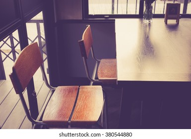 Table and chairs in cafe side the window vintage color